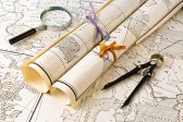 9988907-old-maps-in-rolls-with-magnifier-and-compass